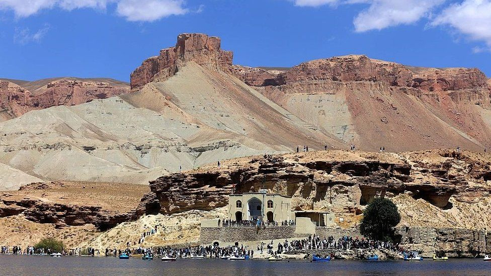 Afghan tourists are pictured at the water's edge of the Band-e Amir lake on the outskirts of Bamiyan on August 29, 2014