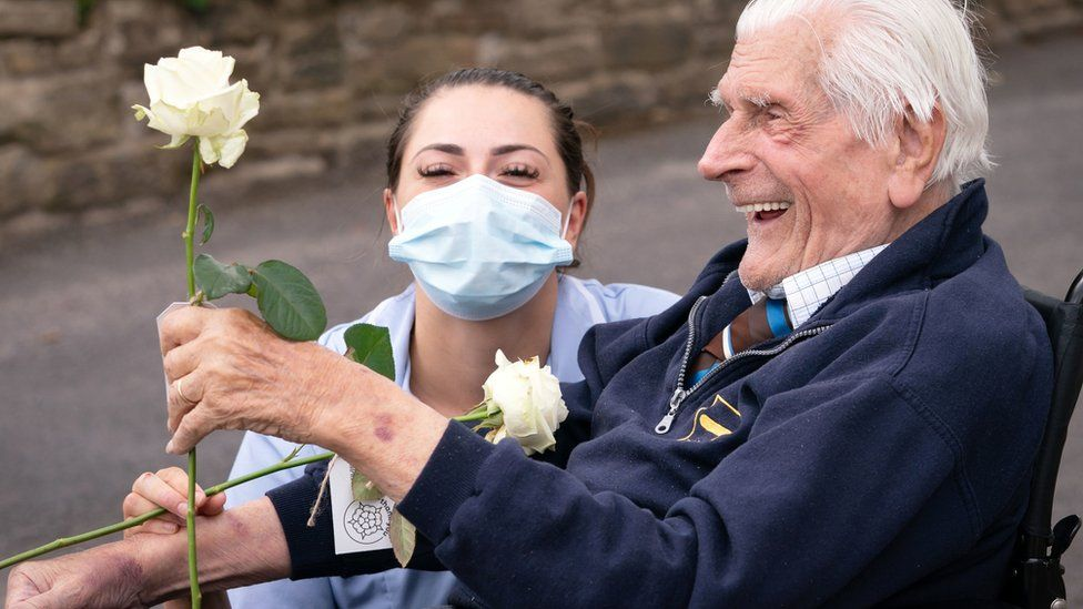 """Health Care Assistant Rose Waddington and ninety-eight-year-old resident John Kykot are pictured with """"thank you"""" white roses that were presented to them by the Mayor of West Yorkshire Tracy Brabin at Norwood House Nursing Home in Keighley, as part of the first-ever national Thank You Day"""