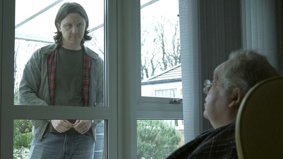 A care home resident conversing with a visitor through the window in Channel 4's Help