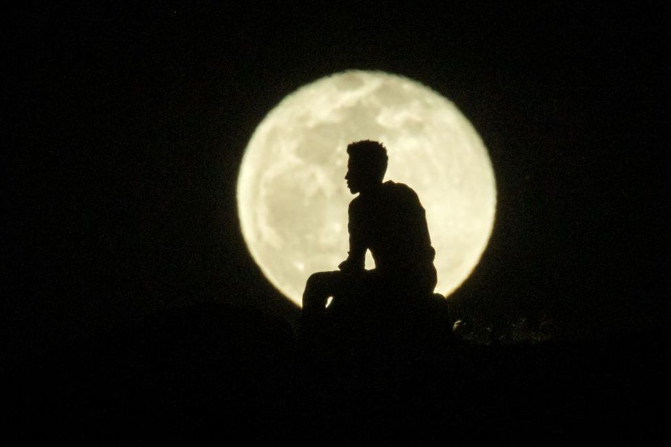 A man's silhouette is seen against a bright, full moon.