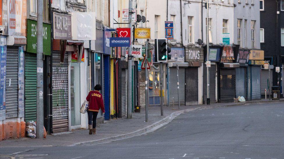 woman walking past closed shops