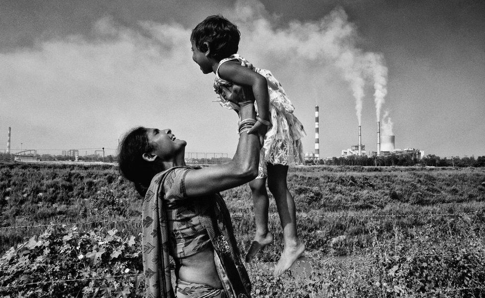 A woman carries a child with a thermal power plant in the background