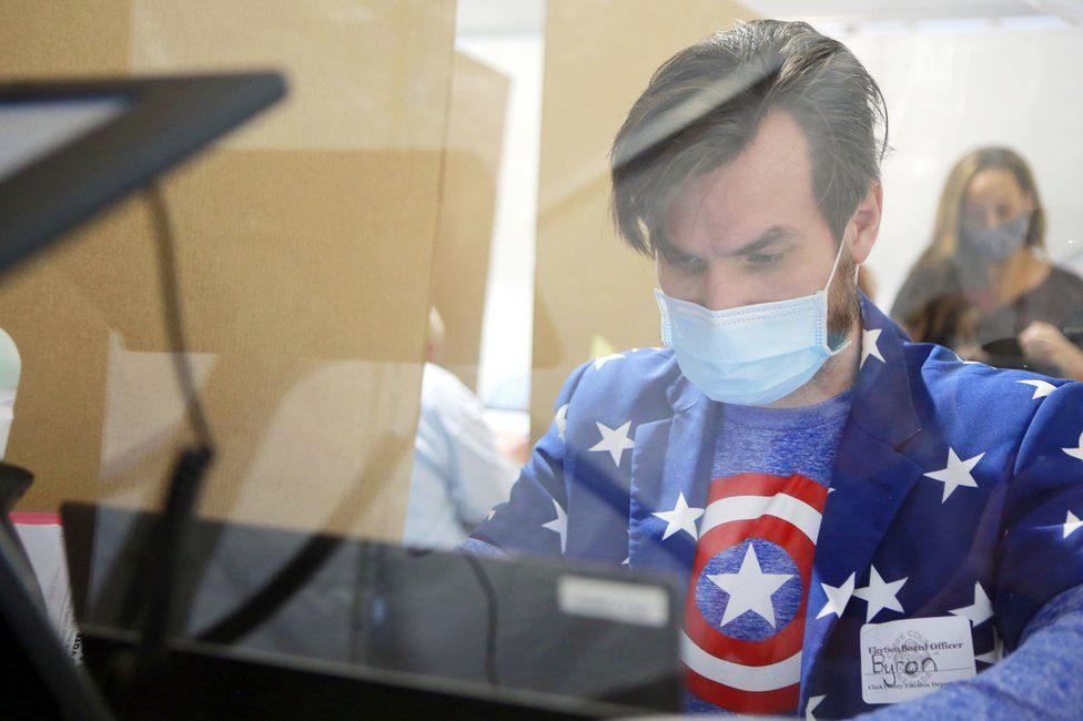 A poll worker is seen behind protective plexiglass
