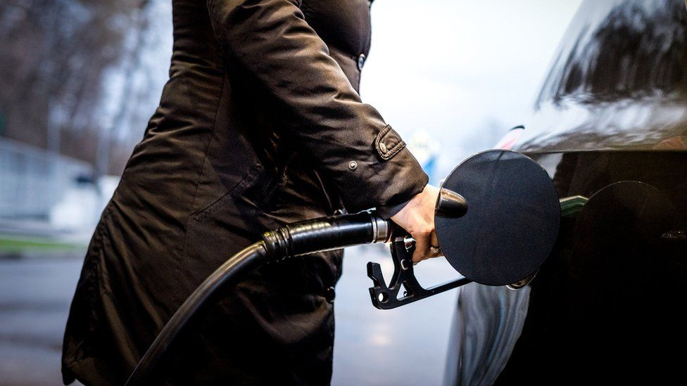 Woman wearing a coat filling up a car with fuel.