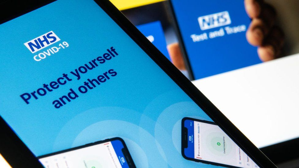 The NHS Covid-19 app logo is seen on a smartphone, with branding from the website for test and trace behind it