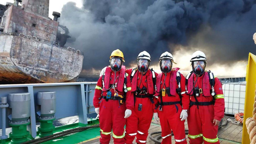 """It shows four Chinese rescuers posing for a picture before boarding the burning oil tanker """"Shanchi"""" at sea off the coast of eastern China, a day before the Iranian oil tanker burst into flames from end to end and sank."""