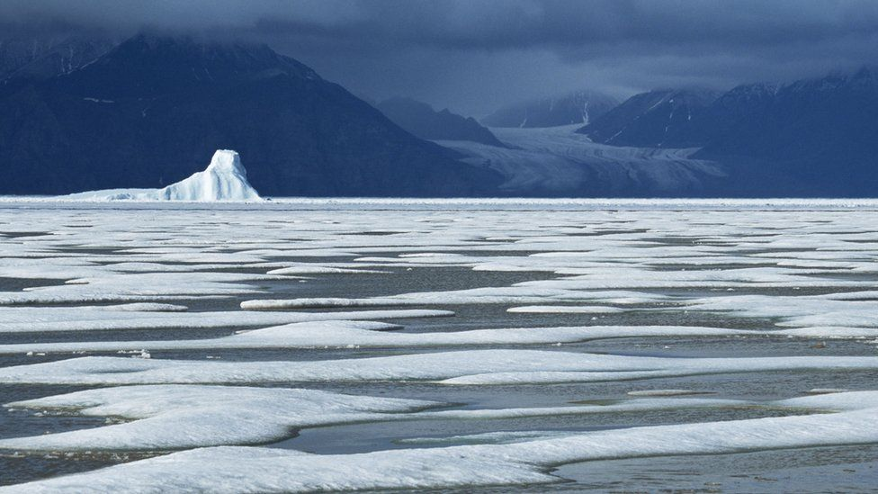 50 metre tall iceberg trapped in the frozen sea of Eclipse Sound Baffin Island, Canada