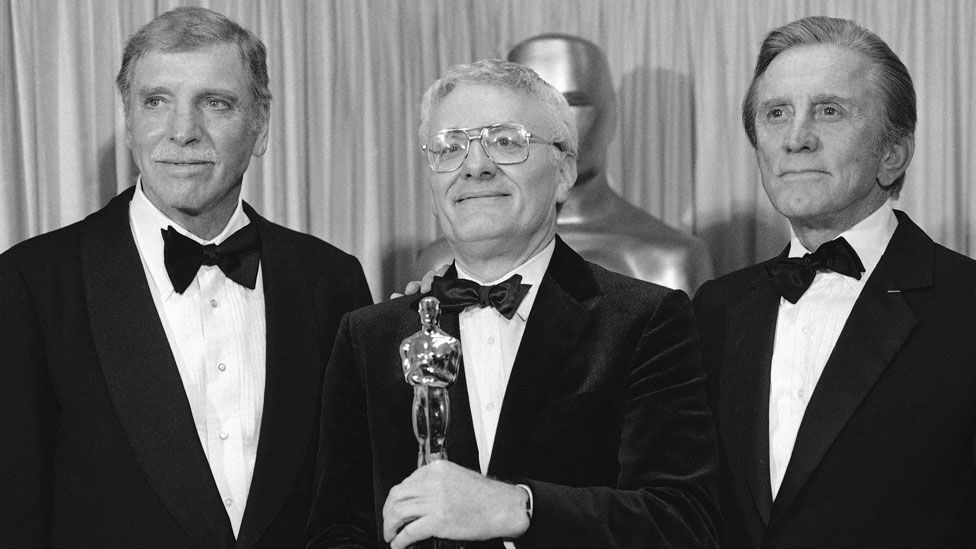 Actors Burt Lancaster [L] and Kirk Douglas [R] presented Sir Peter with his Oscar in 1985 for Amadeus