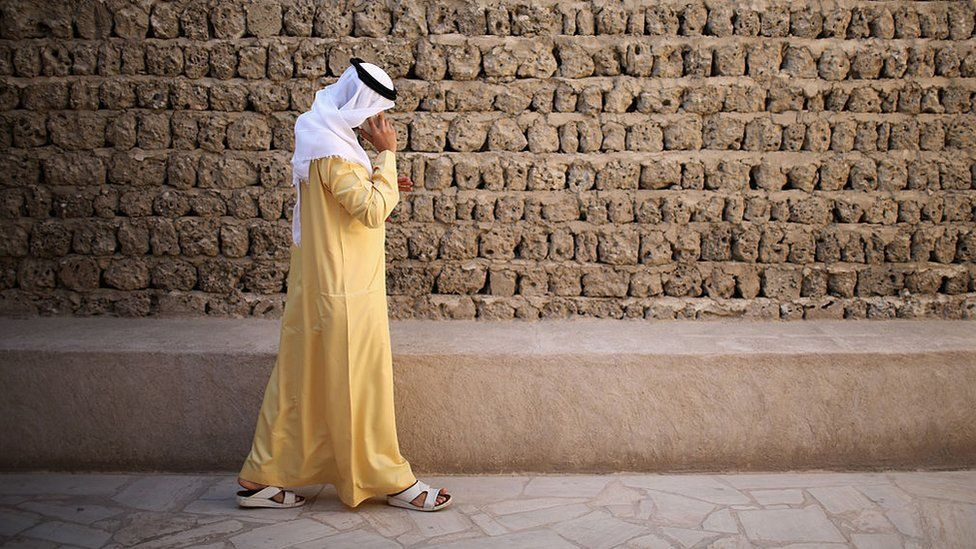 A man talks on his mobile phone as he walks through the Dubai Heritage Village on 13 November 2013 in Dubai, United Arab Emirates