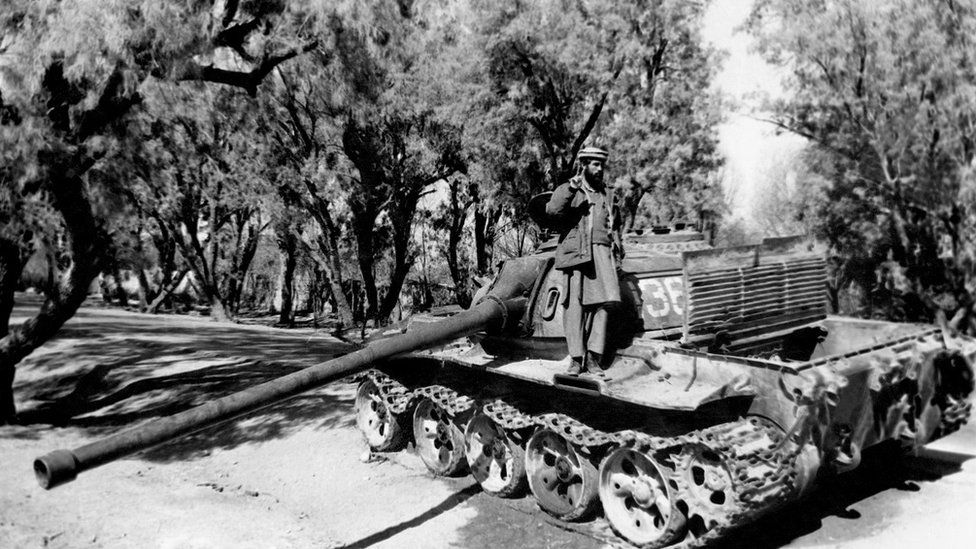 A Mujahideen (mujahidin) stands on a Soviet tank on February 7, 1989 in Torkham, east of Jalalabad, after its capture. (Photo credit should read -/AFP/Getty Images)
