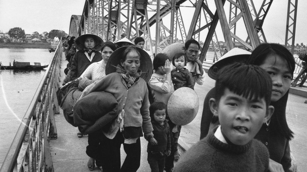 9th February 1968: A group of Vietnamese refugees crossing a bridge over the Perfume River