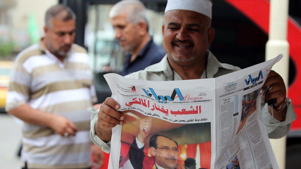 Man reading a newspaper in Iraq