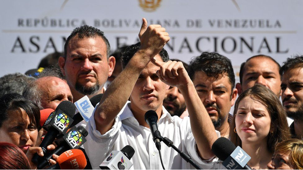 Venezuela's National Assembly president Juan Guaido points at his wrist as he speaks before a crowd of opposition supporters during an open meeting in Vargas