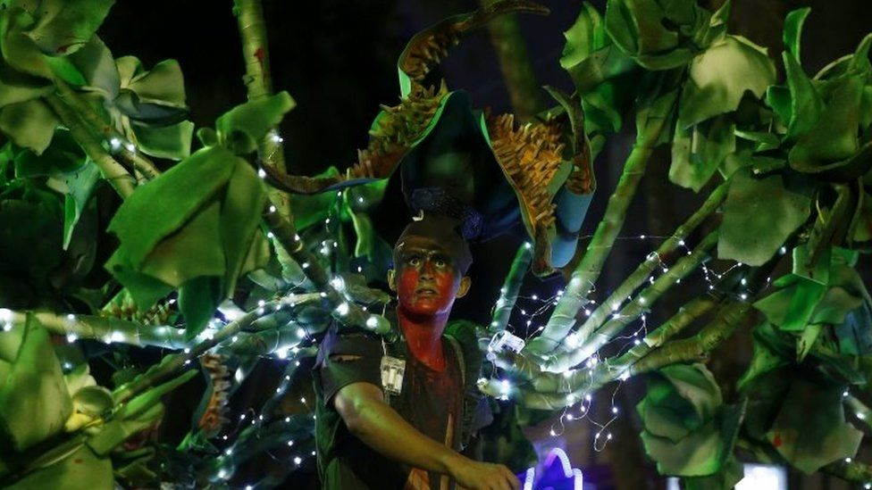 A man disguised as a man-eating tree walks among people at the parade in Medellín
