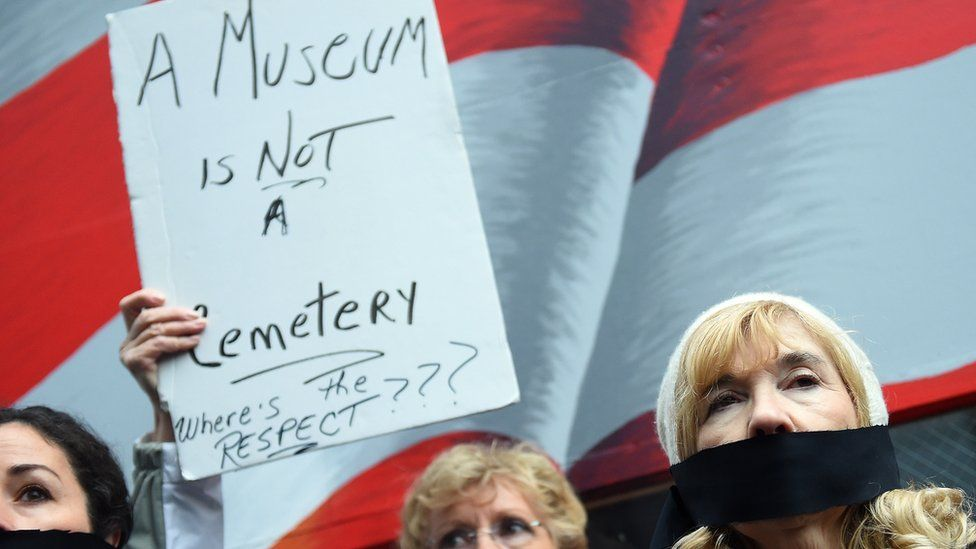 """Protestors hold a """"museum is not a cemetery"""" sign in protest"""