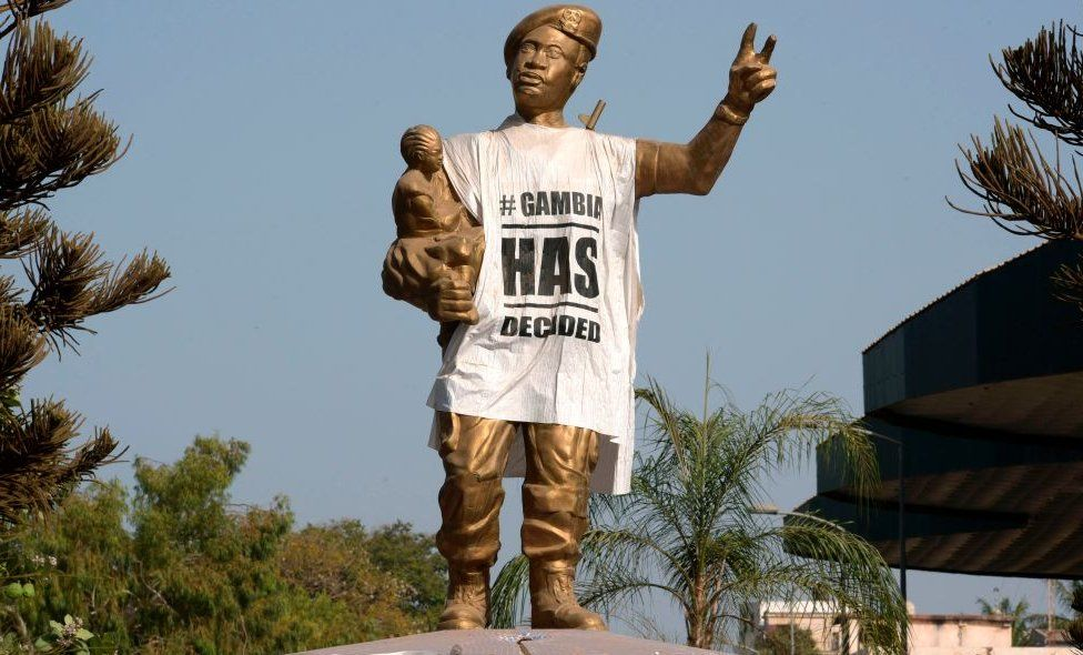 A figure of the Arch 22 monument to mark the July 22, 1994 bloodless coup led by former President Yahya Jammeh is draped with a shirt-shaped banner reading 'Gambia has decided', in Banjul on April 3, 2017