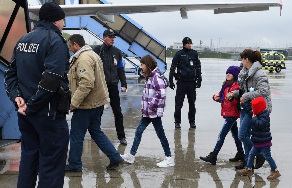Police officers escort rejected asylum seekers to a plane at Franz-Josef-Strauss airport in Munich, southern Germany, on December 9, 2015