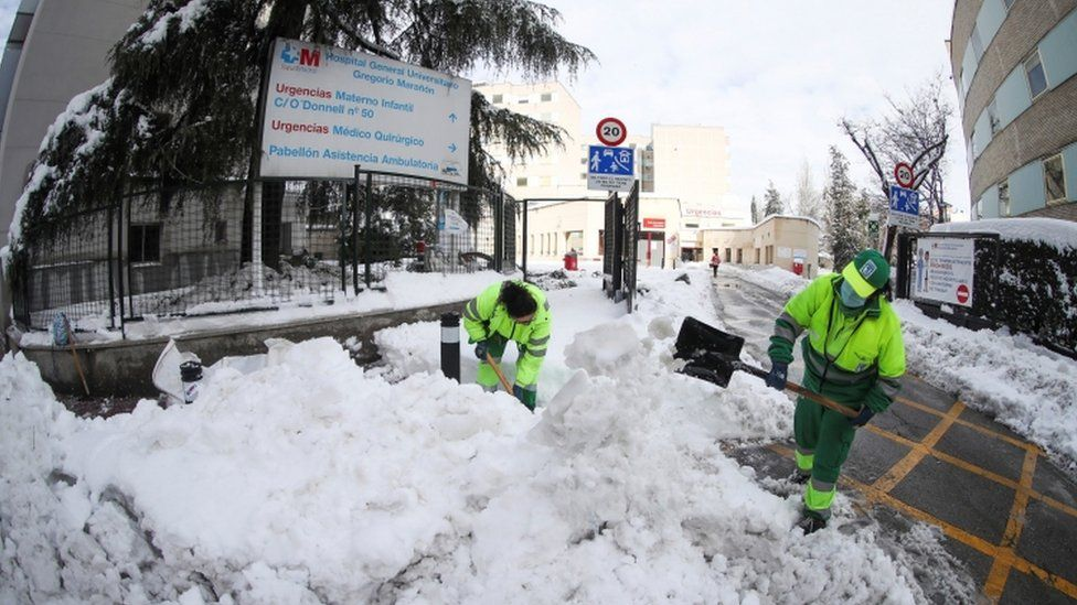 Municipal workers clear snow at entrance to Gregorio Maranon Hospital in Madrid on 10 January 2021