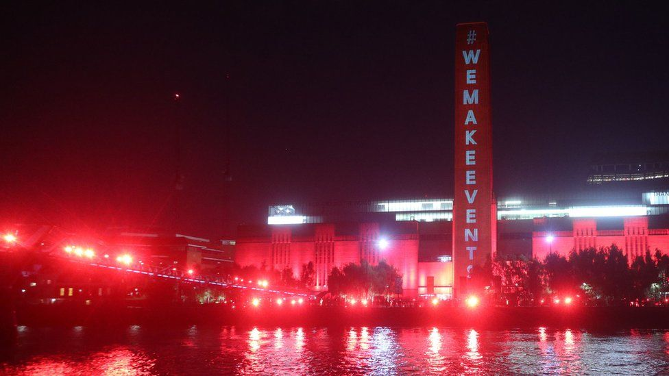 The Tate Modern and Millennium Bridge lit up in red