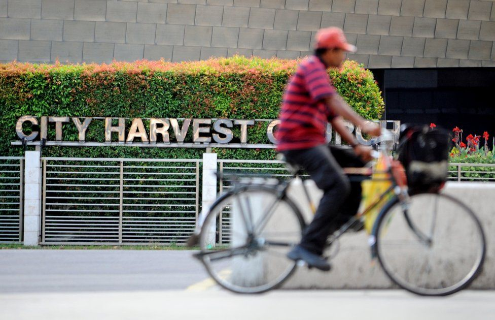 A cyclist rides past the City Harvest Church in Singapore on 26 June 2012.