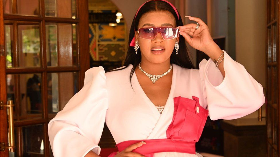 A glamourous lady dressed in pink, wearing sunglasses and diamond jewellery poses for a picture with her hand on her hip.