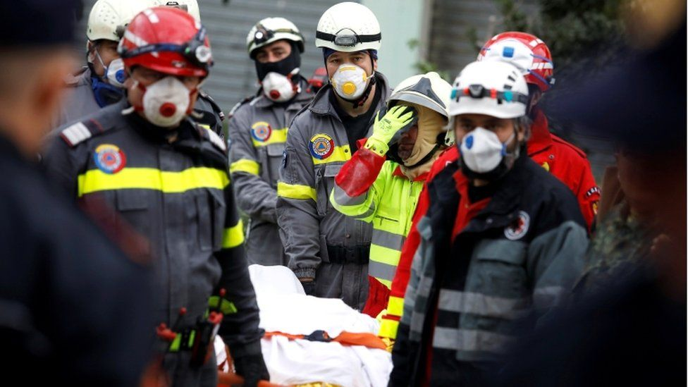 Emergency personnel carry a body on a stretcher as they work in a collapsed building in Durres