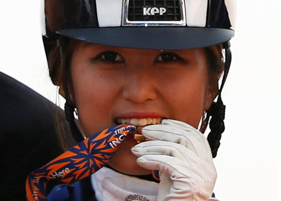 South Korea's , bites her gold medal as she poses after winning the equestrian Dressage Team competition at the Dream Park Equestrian Venue during the 17th Asian Games in Incheon, South Korea, on 20 September 2014.