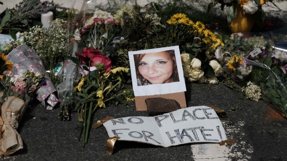 A memorial shows a picture of Heather Heyer at her place of death with 'no place for hate' sign by it.