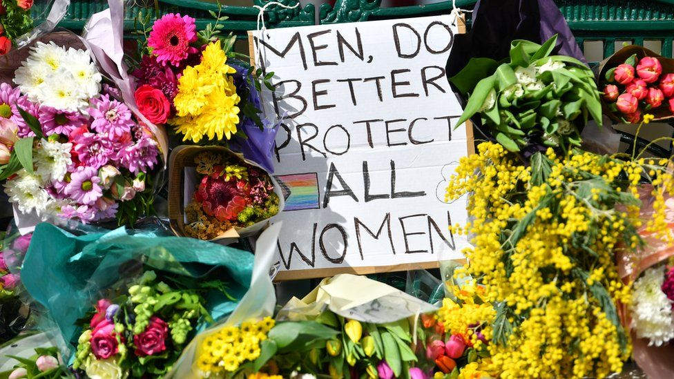 "Flowers and a sign that reads ""Men, Do Better. Protect All Women"" in memory of Sarah Everard on Clapham Common, London, on 13 March 2021"