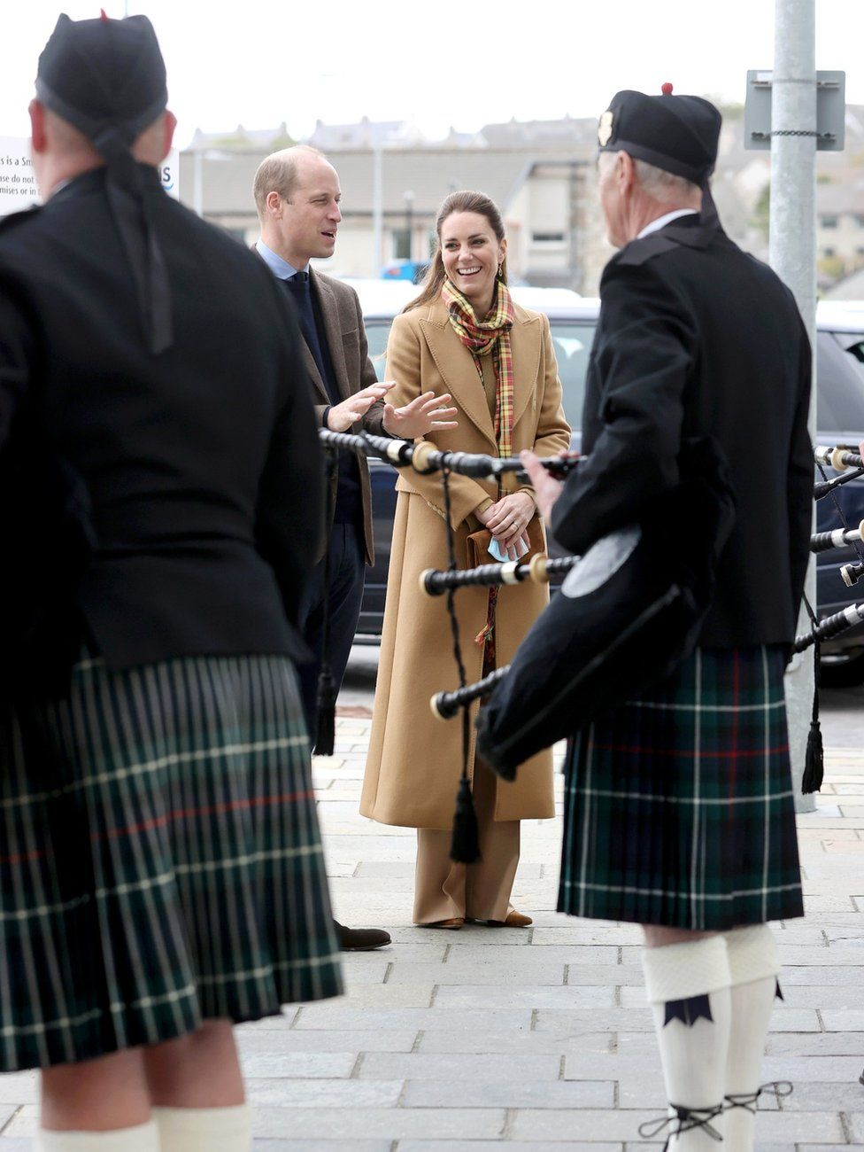 The couple speak to pipers as they arrive to open the hospital