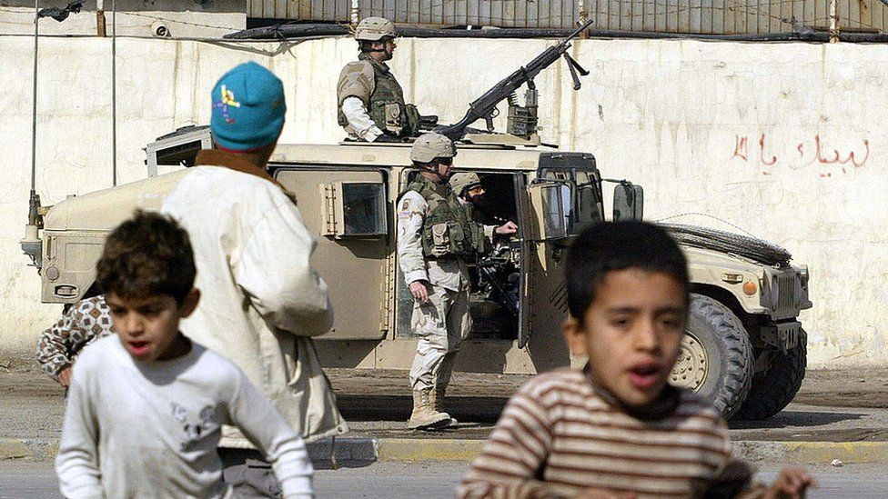 Boys run as a US soldier gets out of an armoured vehicle in Sadr City, Baghdad, 31 December 2004