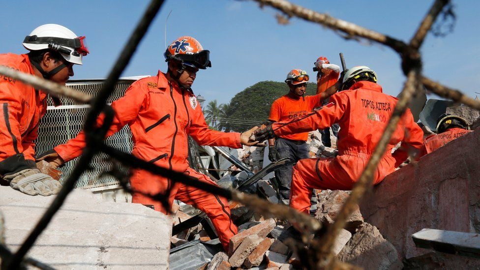men in jumpsuits passing rubble along a human chain