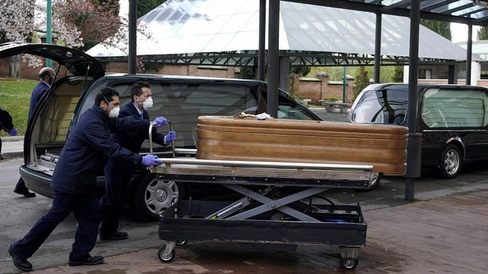 Employees of a mortuary enter the crematorium of La Almudena cemetery with a coffin of a person who died of coronavirus disease in Madrid, March 23, 2020
