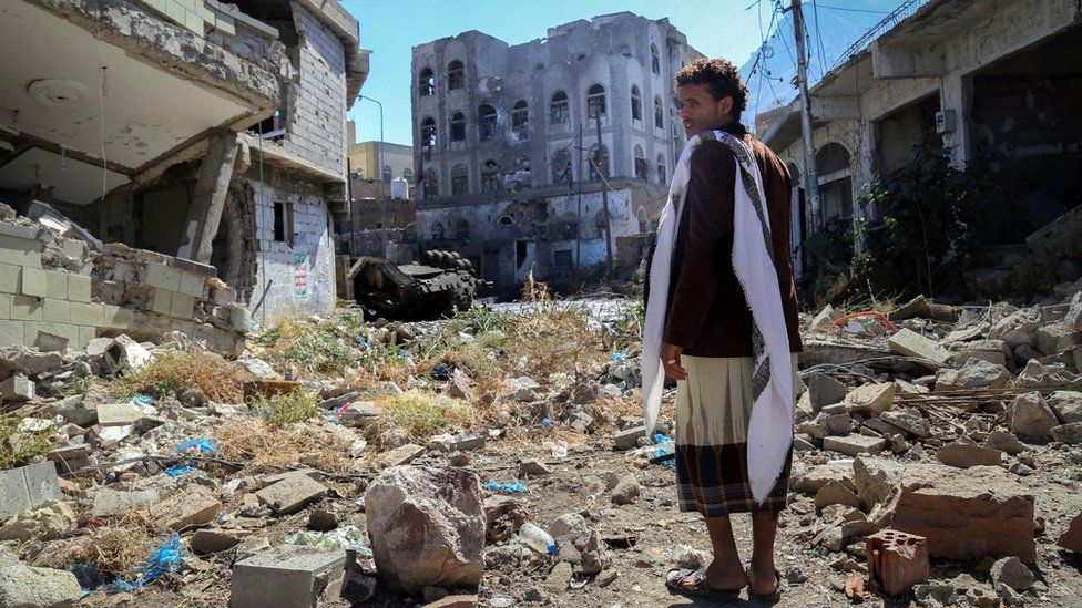 A Yemeni man inspects damage on a street following clashes between pro-government militiamen and Houthi rebels in Taiz (22 November 2016)