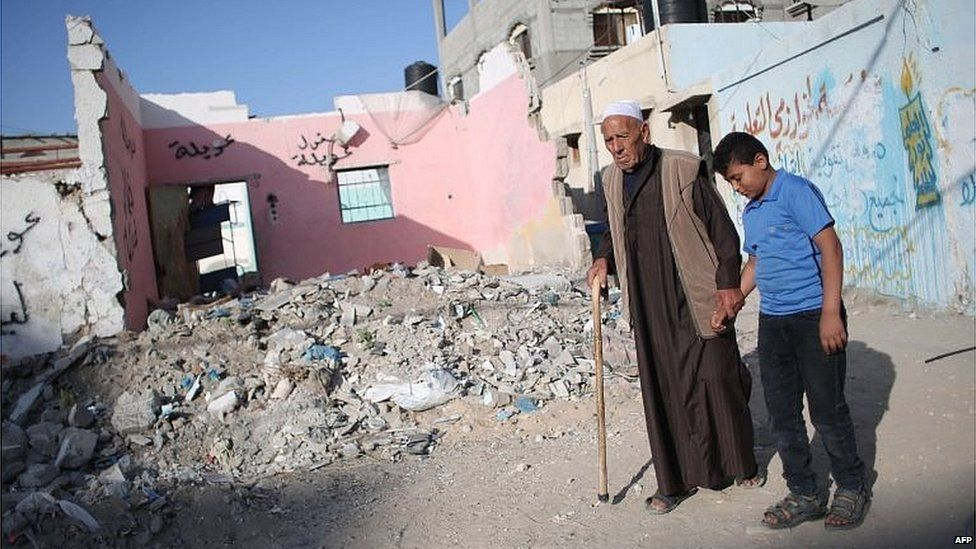 Palestinians walk past rubble from 2014 war in Gaza