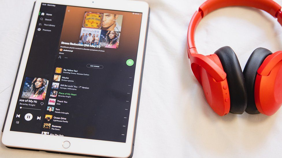 A pair of red headphones lies on a white bedsheet next to an iPad showing a Spotify playlist with many songs popular in the early 2000s
