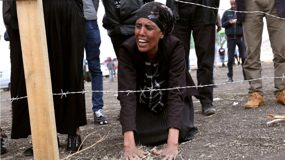 A family member of the Ethiopian Airlines crash victims mourns at the fenced-off accident site
