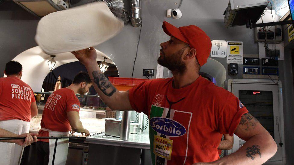 A pizza-maker prepares a pizza in Naples