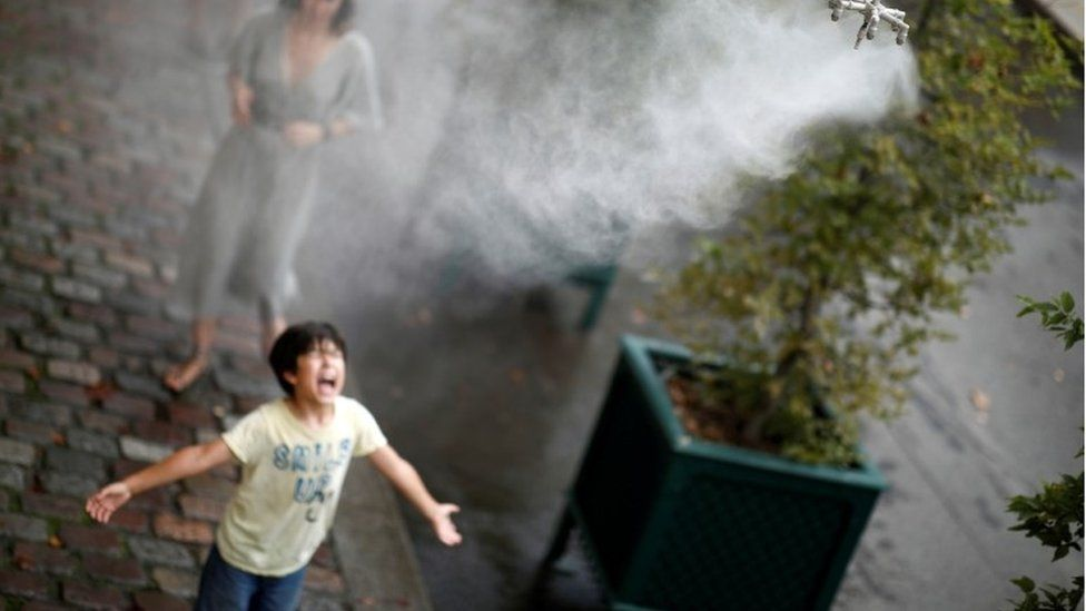 A child cools off under a water spray as a heatwave rolls over Paris, France, August 8, 2020.