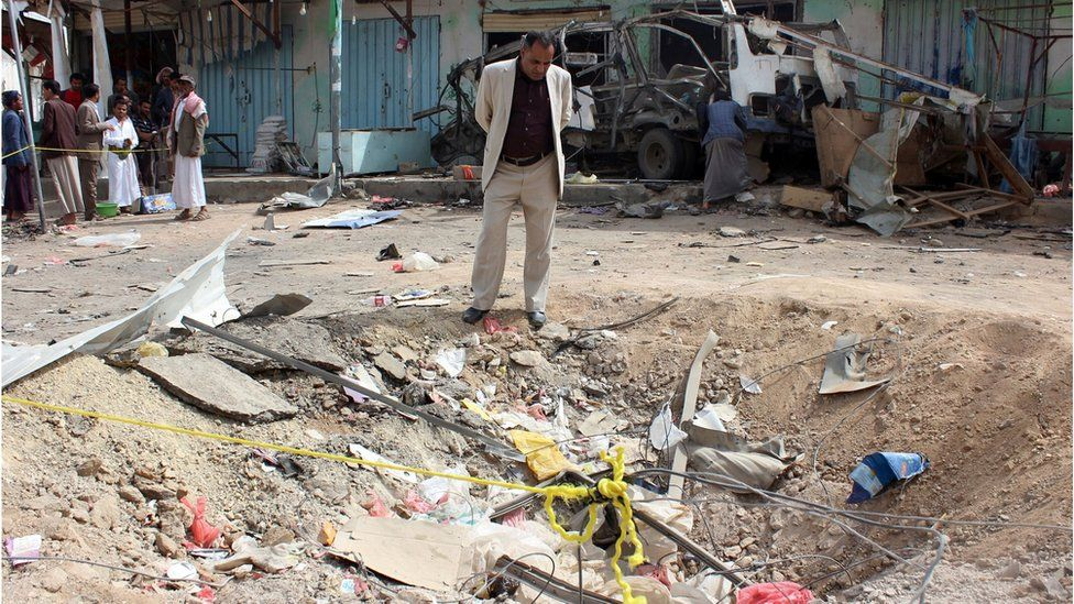A Yemeni man stands beside the crater left by a Saudi-led coalition air strike on Dahyan, Yemen (10 August 2018)