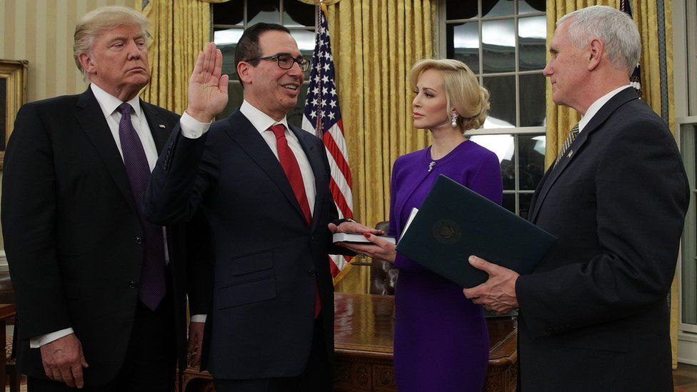 Former investment banker for Goldman Sachs Steven Mnuchin (2nd left) participates in a swearing-in ceremony, conducted by Vice President Mike Pence (right), as fiancée Louise Linton (3rd left) and President Donald Trump (left) look on in the Oval Office of the White House on 13 February 2017 in Washington, DC.