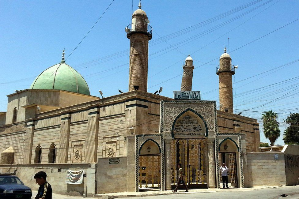 People walk in front of the Great Mosque of al-Nuri in Mosul, Iraq (9 July 2014)