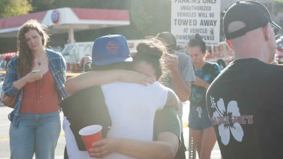 People hug each other outside Trader Joe's in Los Angeles. Photo: 21 July 2018