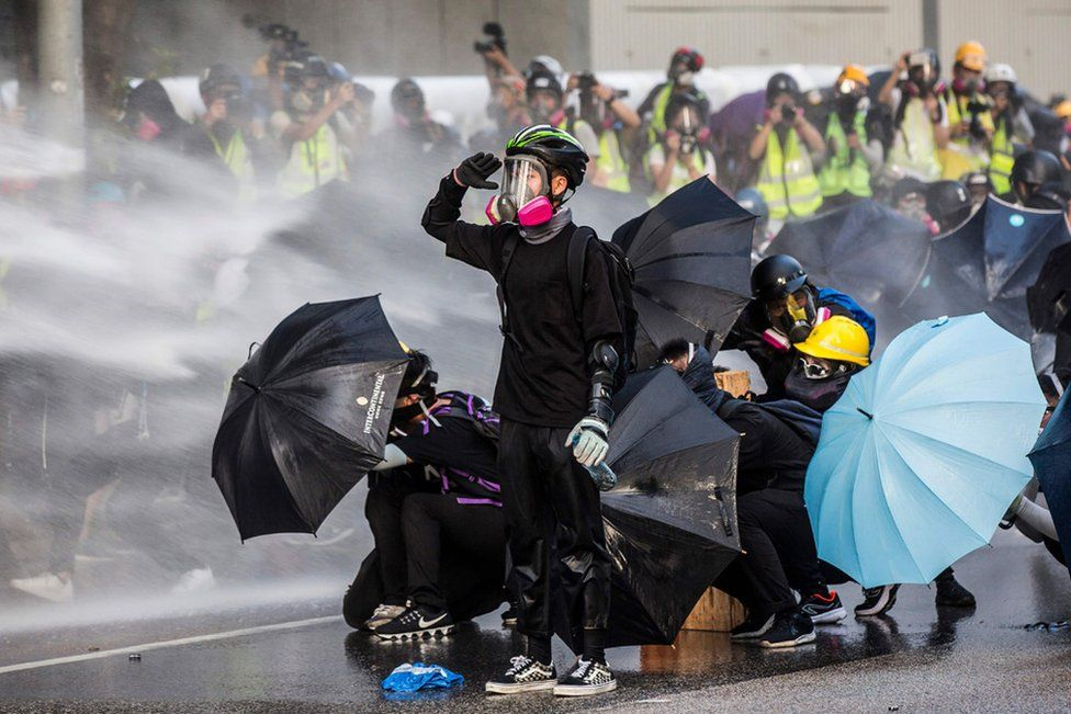 Pro-democracy protesters react as police fire water cannons outside the government headquarters in Hong Kong, 15 September 2019.