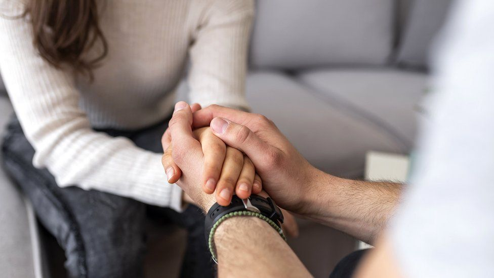 A woman sat on a sofa holding hands with a therapist