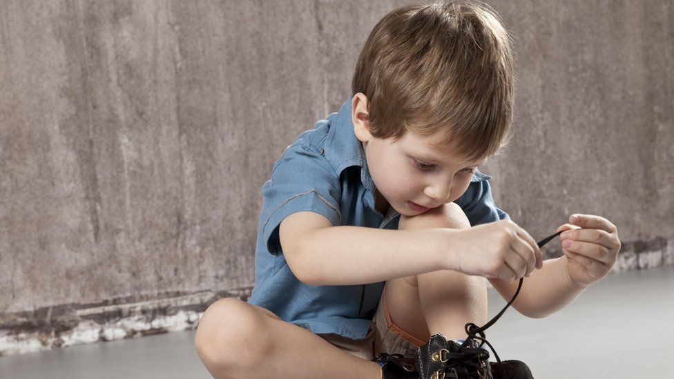 A boy tying his shoes