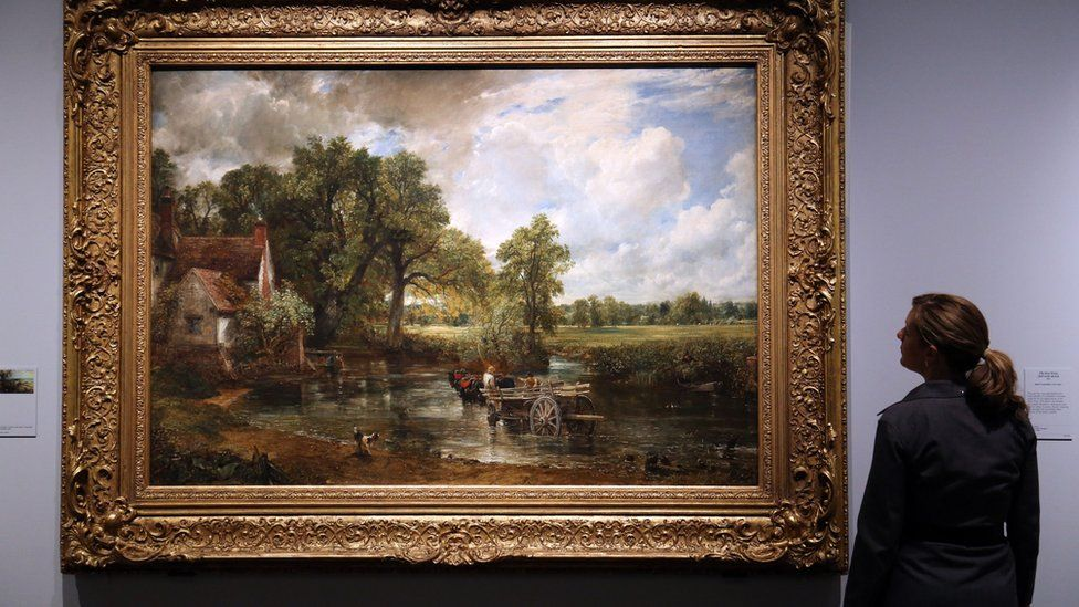 A V&A museum employee looking at John Constable's 1821 painting The Hay Wain