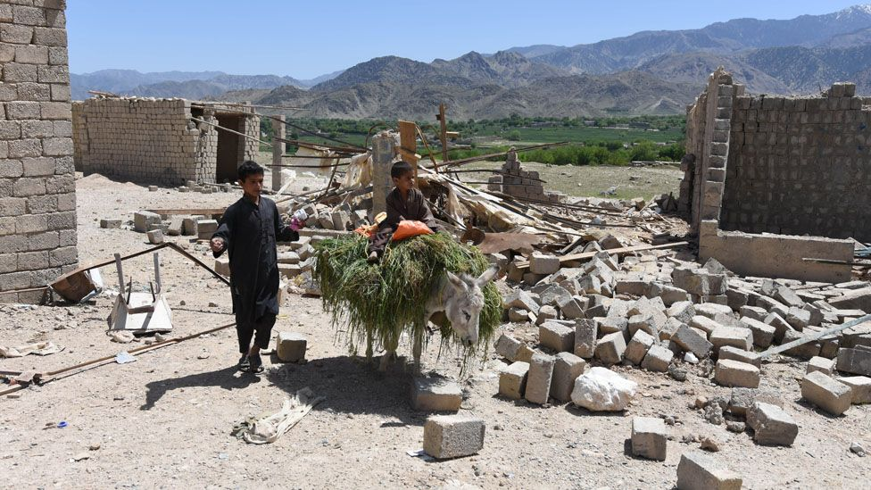 Afghan boys walk amid the rubble of shops in Shadal bazaar after the US military dropped a bomb