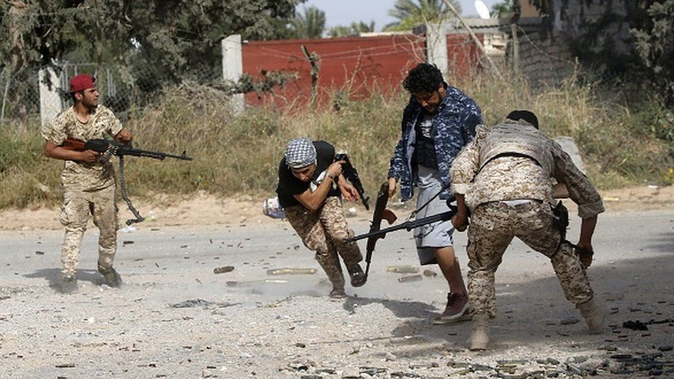 Libyan fighters loyal to the Government of National Accord (GNA) run as they fire their guns during clashes