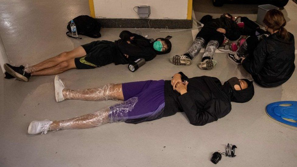 Protesters sleep on the floor of a parking lot inside the Hong Kong Polytechnic University
